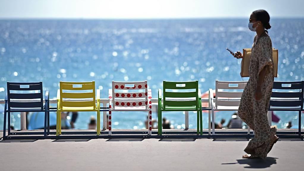 Eine Frau geht auf der Strandpromenade an der französischen Riviera an Stühlen vorbei.