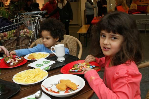 Viola, 5, (rechts) und Sindi Stöckli, 2, haben ihre Lebkuchenherzen bereits fertig verziert und stärken sich jetzt im Restaurant