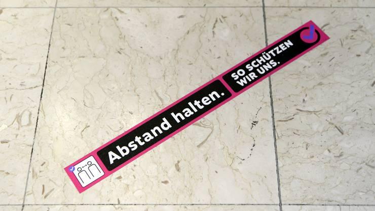 Kleber der Kampagne des Bundesamts für Gesundheit zur Eindämmung der Coronapandemie am Boden eines Geschäfts in Bern.