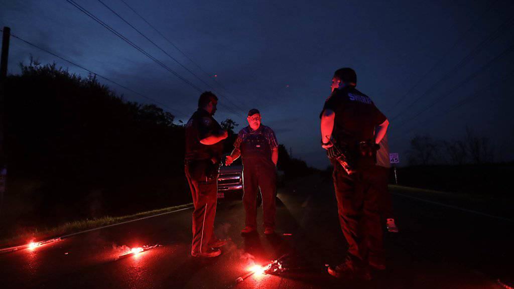Polizisten sichern die Zugangsstrassen zum Chemiewerk, aus dem nach Explosionen gefährlicher Rauch austritt.