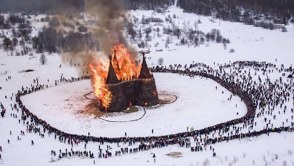 Menschen beobachten die Verbrennung einer schlossförmigen Holzkonstruktion als Teil der Feierlichkeiten zum Masleniza-Fest im Nikola-Lenivets-Kunstpark. Foto: Dmitry Serebryakov/AP/dpa