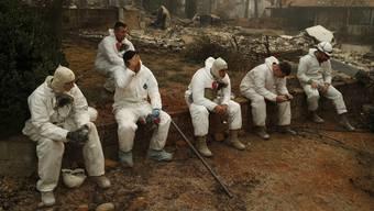 US-amerikanische Nationalgardisten machen eine Pause bei ihrer schwierigen Arbeit, in den Brandruinen nach Leichnamen zu suchen.