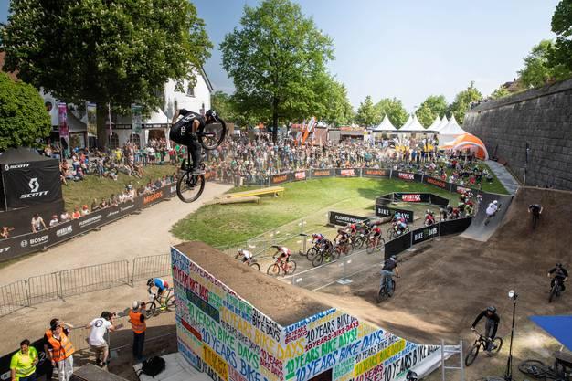 Unten fahren die Teilnehmer des Swiss Bike Cups, oben fliegen die Dirtjumpler durch die Lüfte.
