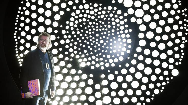 """Olafur Eliasson vor dem """"Algenfenster"""" aus Glaskugeln, die das Zürcher Aussenleben ins Kunsthaus spiegeln."""