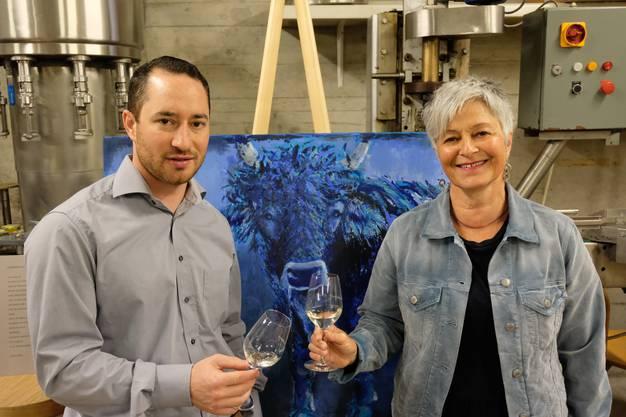 Winzer Robin Haug und seine Mutter Dora Haug posieren vor einem von Dora Haugs Kunstwerken.