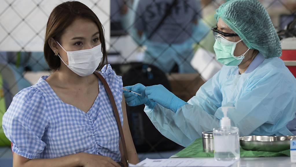 Eine Gesundheitsmitarbeiterin impft eine Frau in Bangkok, die in einer Vergnügungsstätte arbeitet. Foto: Sakchai Lalit/AP/dpa