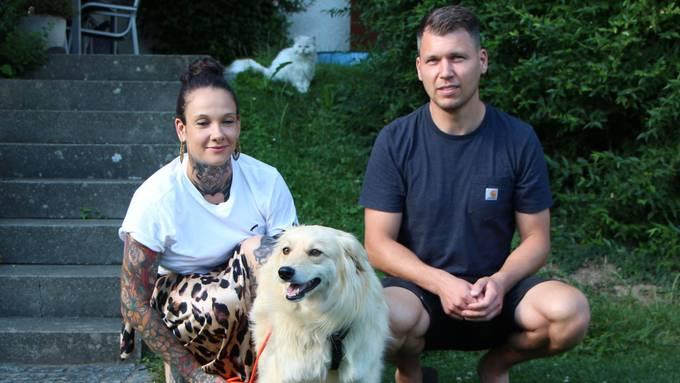 Vivienne Sprang und Florian Lorenz mit Nantha am Sicherheitsgeschirr im Garten in Kirchdorf, beobachtet von der Katze.