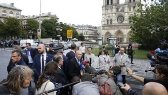 Innenminister Gerard Collomb (M.) spricht nach der Attacke vor der Kathedrale Notre Dame zu den Medien.