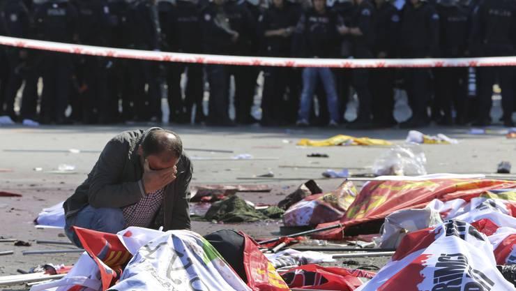 Ein Mann trauert, im Hintergrund die Polizei
