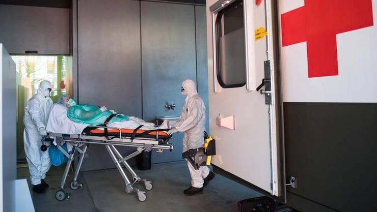 Soldaten der Schweizer Armee beim Transport eines Patienten mit Covid-19 am Eingang der Notaufnahme im Kantonsspital «La Carita» in Locarno. Das Tessin verzeichnet bereits 1211 Infizierte.