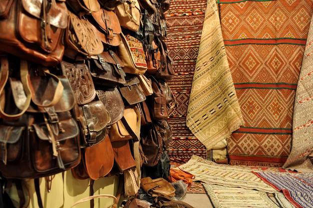 Lederwaren und Teppiche an einem Stand.