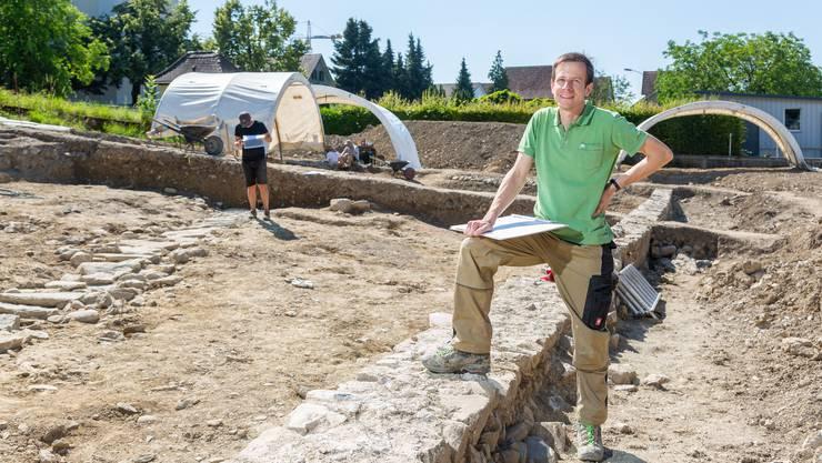 Ausgrabungsleiter Matthias Flück mit dem Fuss auf einer sehr alten Mauer.