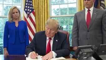 US-Präsident Donald Trump am Mittwoch im Weissen Haus bei der Unterzeichnung des Dekrets zum Stopp der Familientrennungen. Stehend hinter ihm die Ministerin für Innere Sicherheit Kirstjen Nielsen und Vizepräsident Mike Pence.