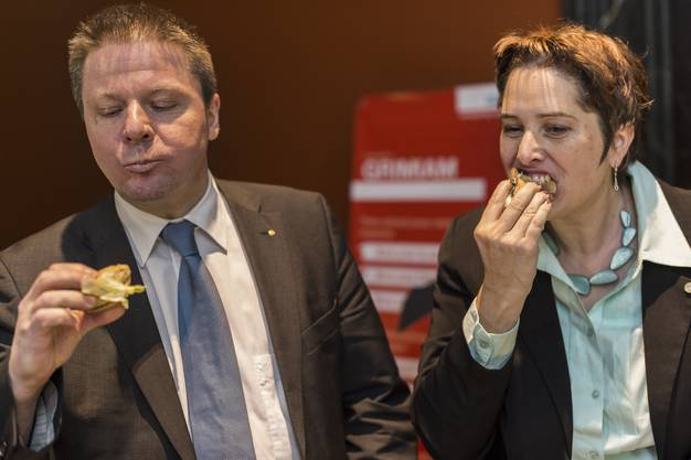 Nationalraetin Isabelle Chevalley, GLP-VD, rechts, und Martin Baeumle, GLP-ZH, beissen herzhaft in einen Hamburger, welcher anstelle von Fleisch mit Mehlwuermern hergestellt wurde.