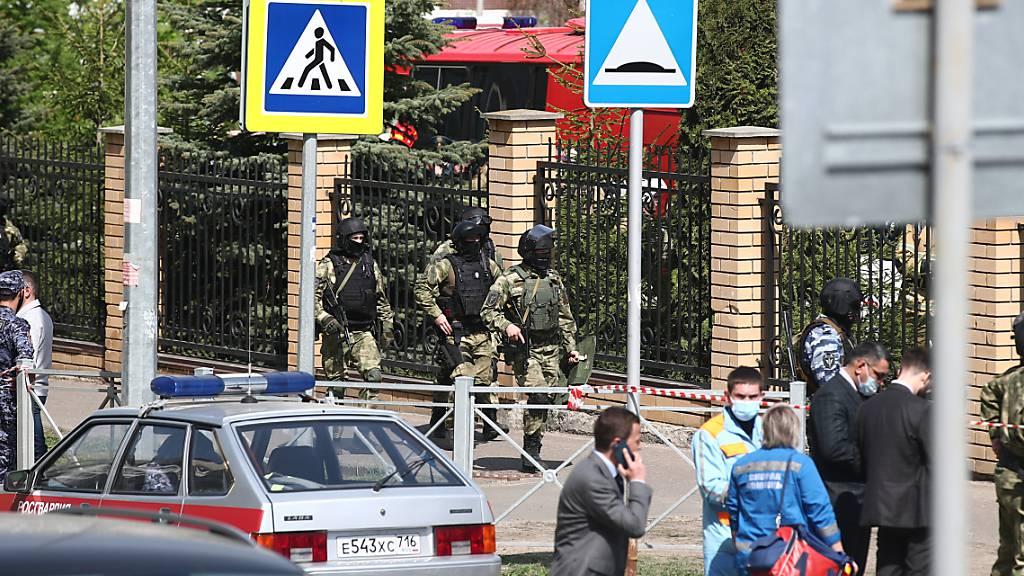 Bewaffnete Einsatzkräfte gehen zum dem Gymnasium Nummer 175. Foto: Yegor Aleyev/Tass/dpa