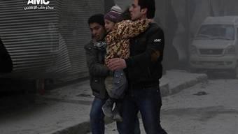 Männer in Aleppo bringen Kinder in Sicherheit (Archiv)
