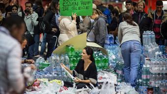 Flüchtlinge bekommen bei der Ankunft Nahrungsmittel und Kleider.