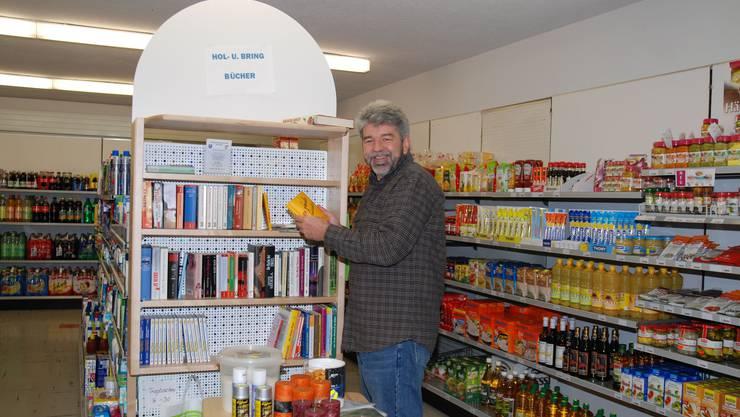 Peter Kalt, Präsident der Ladengenossenschaft Ittenthal, zeigt auf das neue Angebot im kleinen Dorfladen: eine Büchertauschecke. sh