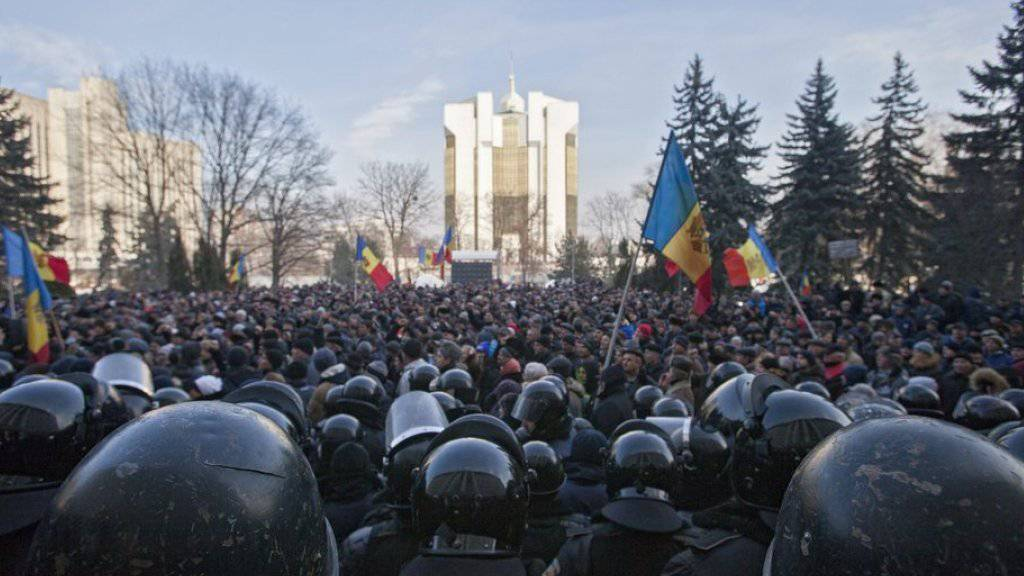 Polizisten treten vor dem Parlamentsgebäude in Chisinau den Demonstranten entgegen