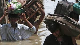 Einwohner eines überschwemmten Dorfes bringen Habseligkeiten in Sicherheit