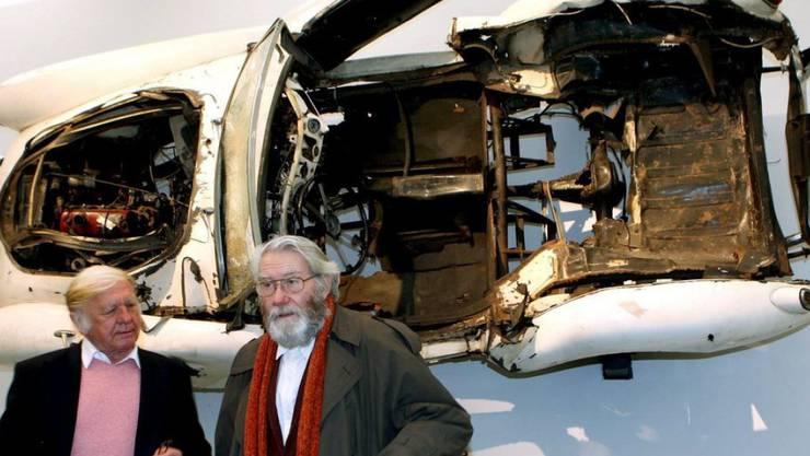 Heinz Mack (links) und Otto Piene stehen 2006 im Kunstpalast Düsseldorf an einer ZERO-Ausstellung vor einem zerstörten Rennwagen des Künstlers Arman (Archiv)