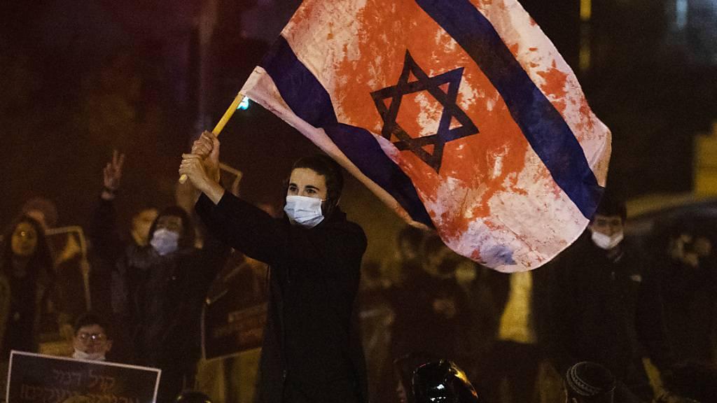 Ein Jugendlicher schwenkt bei einer Demonstration gegen die Polizei eine israelische Flagge, die mit roter Farbe beschmiert ist.
