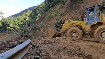 Ein Bulldozer räumt eine durch einen Erdrutsch beschädigte Straße. Zwei durch den Taifun «Molave» verursachte Erdrutsche haben in Vietnam mindestens 13 Menschen getötet. Foto: Bui Van Lanh/VNA/dpa