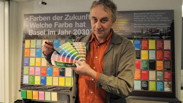 Der Grafiker Markus Urfer zeigt die Pantonefarben, unter denen die Befragten auswählen konnten. Im Hintergrund die Wand bei der GGG.