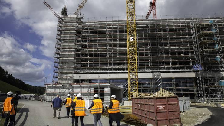 Für Besucher gibt es auf der Grossbaustelle viel zu beobachten: In luftiger Höhe sind Arbeiter mit den letzten Dachaufbauten beschäftigt.