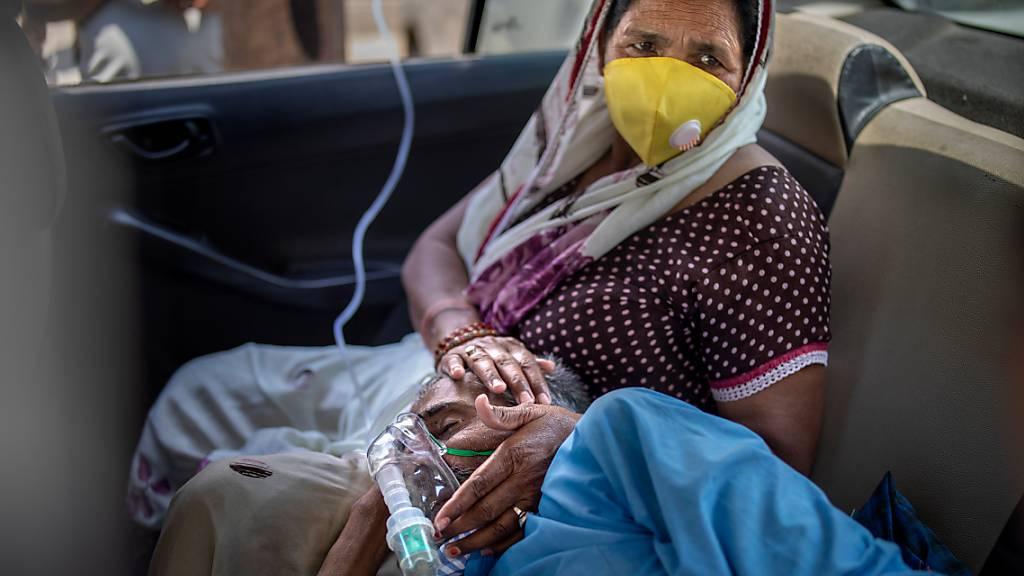 Ein Patient atmet mit Hilfe von Sauerstoff in einem Auto in Neu-Delhi. In Indien hat es den fünften Tag in Folge einen weltweiten Rekord bei den Corona-Neuinfektionen gegeben. Foto: Altaf Qadri/AP/dpa