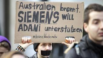 Eine Protestierende hält ein Plakat mit einem Slogan gegen das Siemens Projekt «Adani».