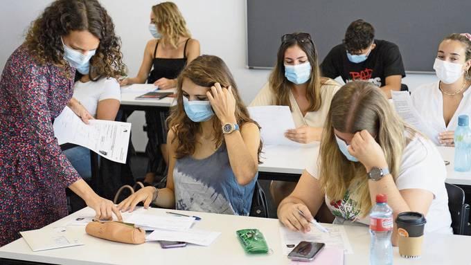 Kampf gegen das Coronavirus: Lehrerin und die Gymnasiasten tragen Maske.
