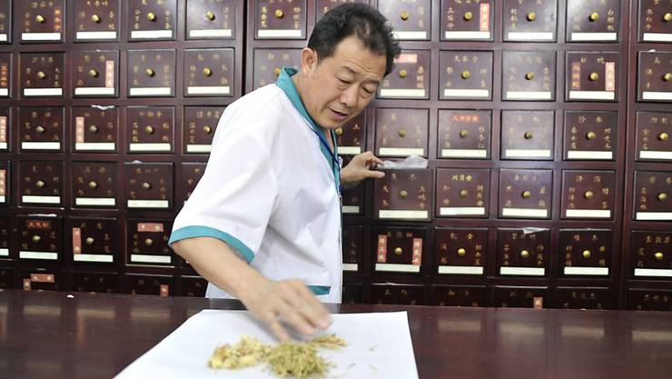 Ein chinesischer Pharmazeut bereitet Traditionelle Chinesische Medizin vor. Die Arzneimittel aus anderen Kulturkreisen können hochaktive Substanzen mit gefährlichen Nebenwirkungen enthalten, wie Forschende der Universität Basel herausgefunden haben. (Archivbild)