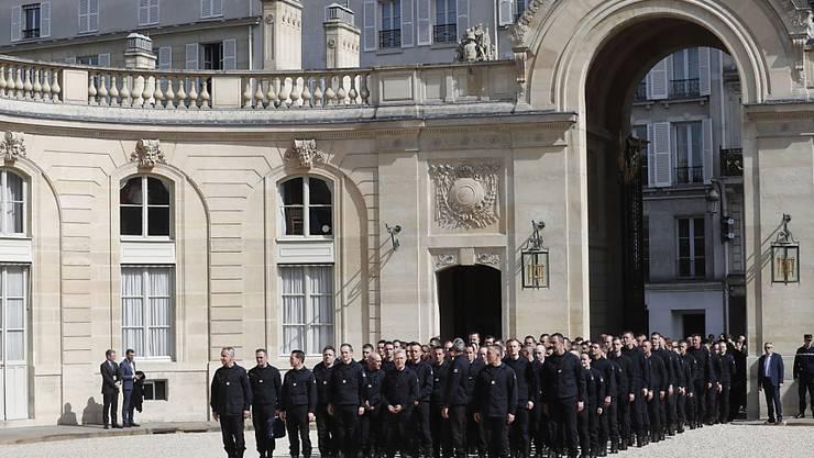 Die Feuerwehrleute warteten vor dem Präsidentenpalast in der Pariser Innenstadt, bevor sie unter Applaus von Umstehenden den Hof des Gebäudes betraten.