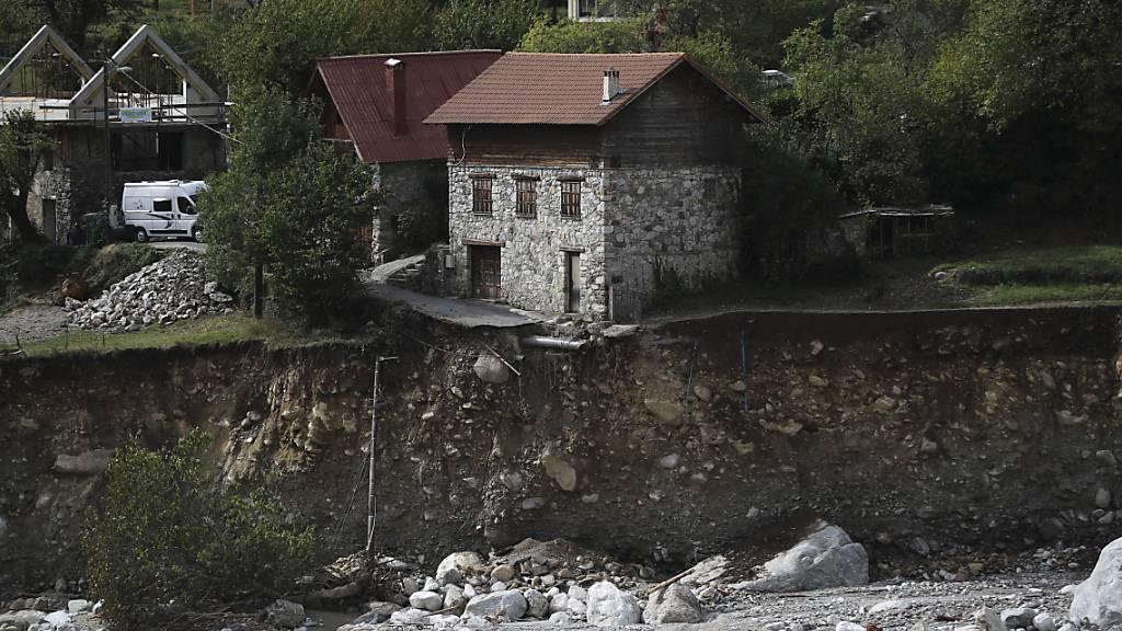 Ein Haus steht an einem Graben nach starken Unwettern. Nach den heftigen Regen-Unwettern laufen in die Aufräumarbeiten. Die Regierung und die EU sicherten den Menschen in den von Hochwasser, Erdrutschen und Sturm heimgesuchten Gebieten ihre Unterstützung zu. Foto: Daniel Cole/AP/dpa