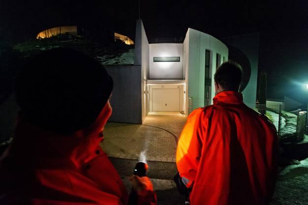 Die beiden Feuerwehrleute leuchten die Häuser mit ihren Taschenlampen an