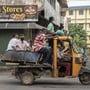 Arbeiterinnen und Arbeiter, die zur Eindämmung des Coronavirus eine Gesichtsmaske tragen, sitzen am Morgen dicht gedrängt auf einem offenen Fahrzeug und fahren zur Arbeit. Die Zahl der bestätigten Corona-Infizierten in Indien lag am Donnerstag bei über 8 Millionen, wobei die täglichen Neuinfektionen in dieser Woche gesunken sind. Foto: R S Iyer/AP/dpa