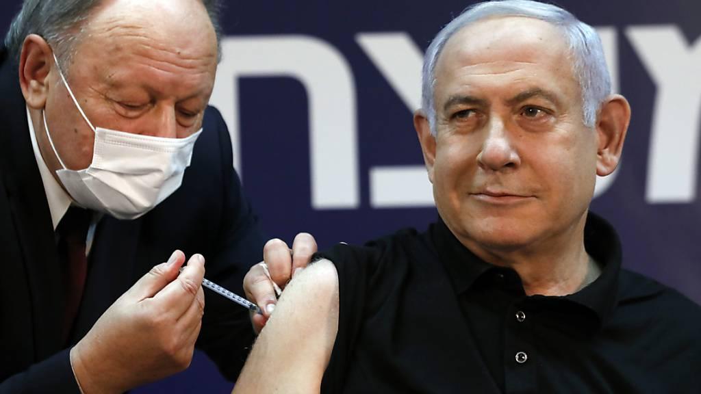 ARCHIV - Benjamin Netanjahu (r.), Ministerpräsident von Israel, wird im Schiba-Krankenhaus gegen Corona geimpft. Foto: Amir Cohen/Reuters/AP/dpa
