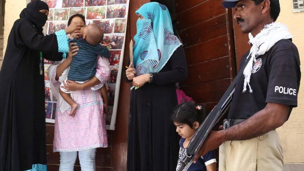 Ein Polizist bewacht die Impfung am Montag in Karachi.