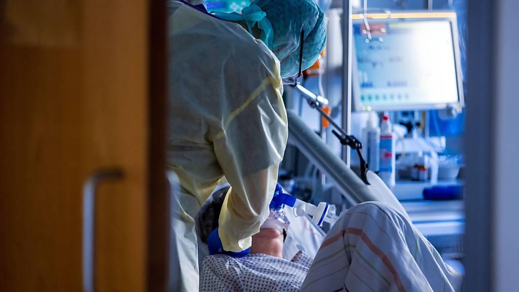 ARCHIV - Eine Pflegekraft versorgt im besonders geschützten Teil der Intensivstation des Universitätsklinikums einen Corona-Patienten. Foto: Jens Büttner/dpa-Zentralbild/dpa