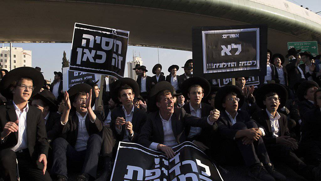 Junge ultraorthodoxe Juden protestieren sitzend auf einer Strasse in Jerusalem gegen die allgemeine Wehrpflicht