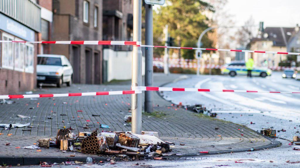 Ein Absperrband der Polizei sperrt in  Bottrop einen Teil der Osterfelder Strasse ab. Auf dem Boden liegen verbrannte Feuerwerkskörper. Ein Autofahrer hatte in der Silvesternacht seinen Wagen gezielt in eine Fussgängergruppe gesteuert und mindestens vier Menschen zum Teil schwer verletzt.