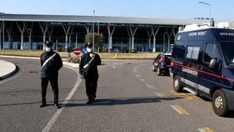 Italienische Polizisten riegeln wegen des Corona-Virus eine Strasse ab. Mehrere Ortschaften wurden unter Quarantäne gestellt.