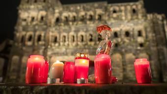 Vor der Porta Nigra brennen Kerzen. Am Nachmittag war ein Mann mit einem Auto durch die Fußgängerzone von Trier gefahren und hat dabei Menschen verletzt und getötet. Foto: Oliver Dietze/dpa