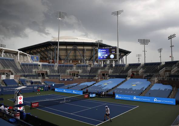 epa08625707 Andy Murray of Great Britain (R) hits a return to Milos Raonic of Canada (L) as dark rain clouds are seen over Arthur Ashe Stadium (Top-Center) during their third round match at the Western and Southern Open at the USTA National Tennis Center in Flushing Meadows, New York, USA, 25 August 2020. Play was temporarily suspended due to heavy rain and lightning. Due to the Coronavirus pandemic, the tournament was relocated to NYC to immediately precede the US Open and to be played without fans.  EPA/JASON SZENES