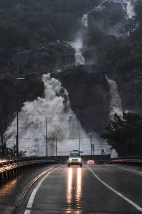 Hinter einem Auto stürzen gewaltige Wassermassen einen Wasserfall hinab – das Bild wurde in Cresciano aufgenommen.
