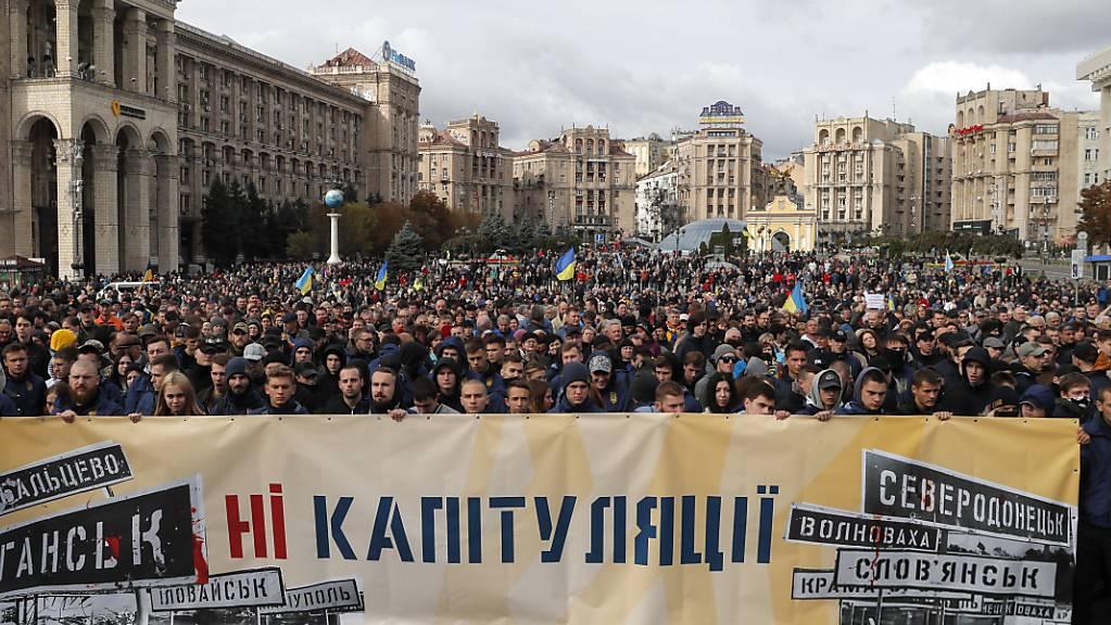 «Nein zur Kapitulation!» steht auf dem Transparent. Tausende Menschen haben am Sonntag in Kiew gegen gegen den Ostukraine-Plan der Regierung demonstriert.