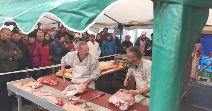 Das Publikum schaut gebannt zu, während die Metzger das Schwein zerteilen.