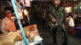 Schwerbewaffnete Soldaten patrouillieren um das von Rothemden besetzte Geschäftsviertel.