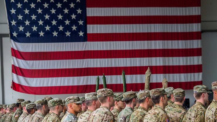 ARCHIV - US-Soldaten stehen während einer militärischen Zeremonie in Bayern vor einer Flagge der Vereinigten Staaten von Amerika. Foto: Nicolas Armer/dpa